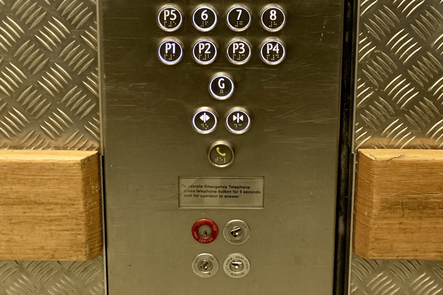 An image of a lift control panel with the ground floor separate, the phone button protected by a ridge, and a series of key holes underneath.