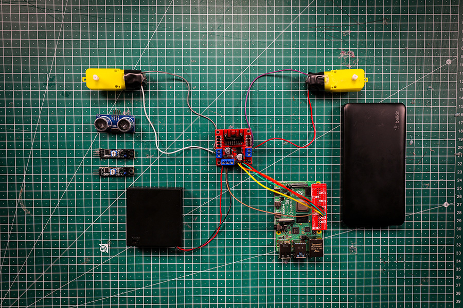 The components that will need to be attached to the robot buggy chassis -  Raspberry Pi, motor controller board, 2 DC motors, ultrasonic distance sensor, 2 line sensors, AA battery holder, USB battery pack