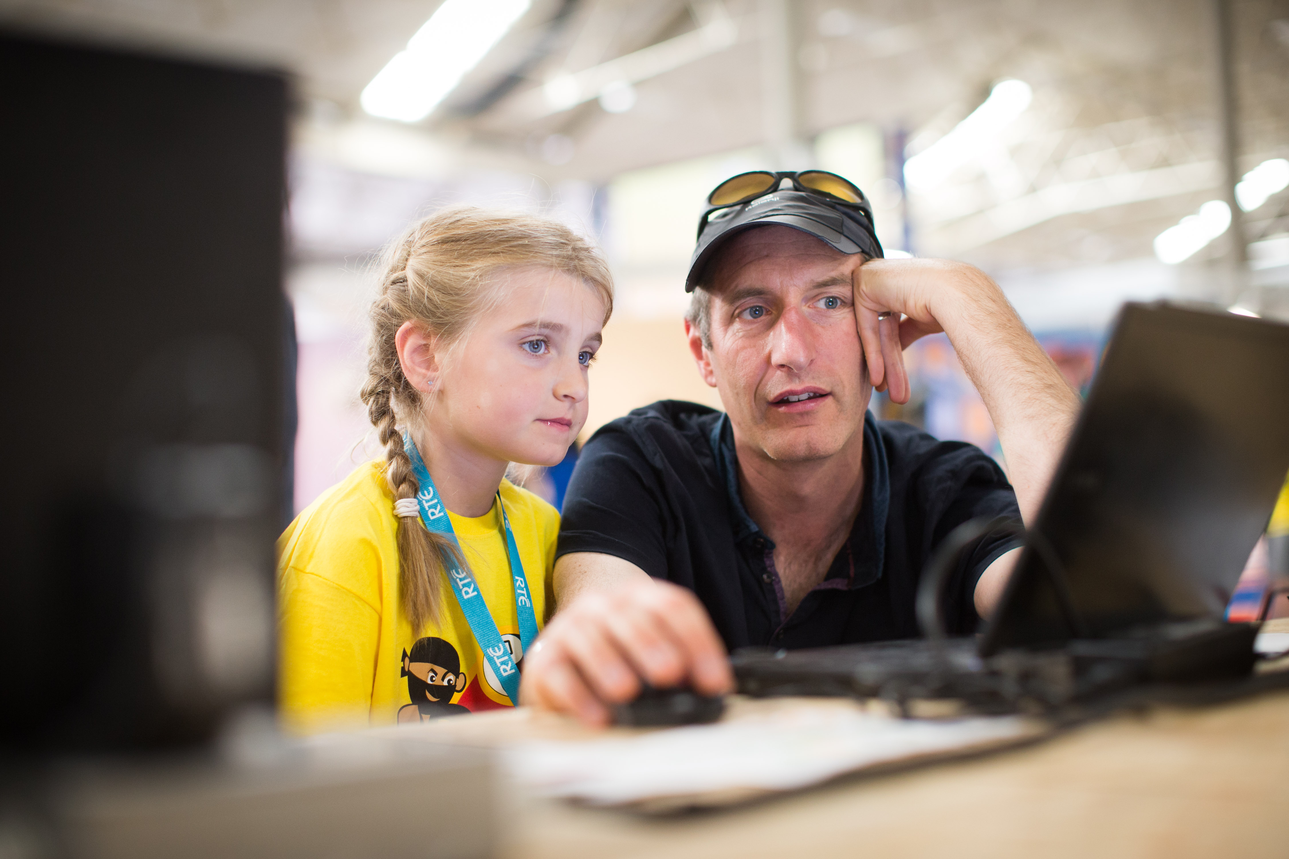 A girl and her father watching an output on a computer screen
