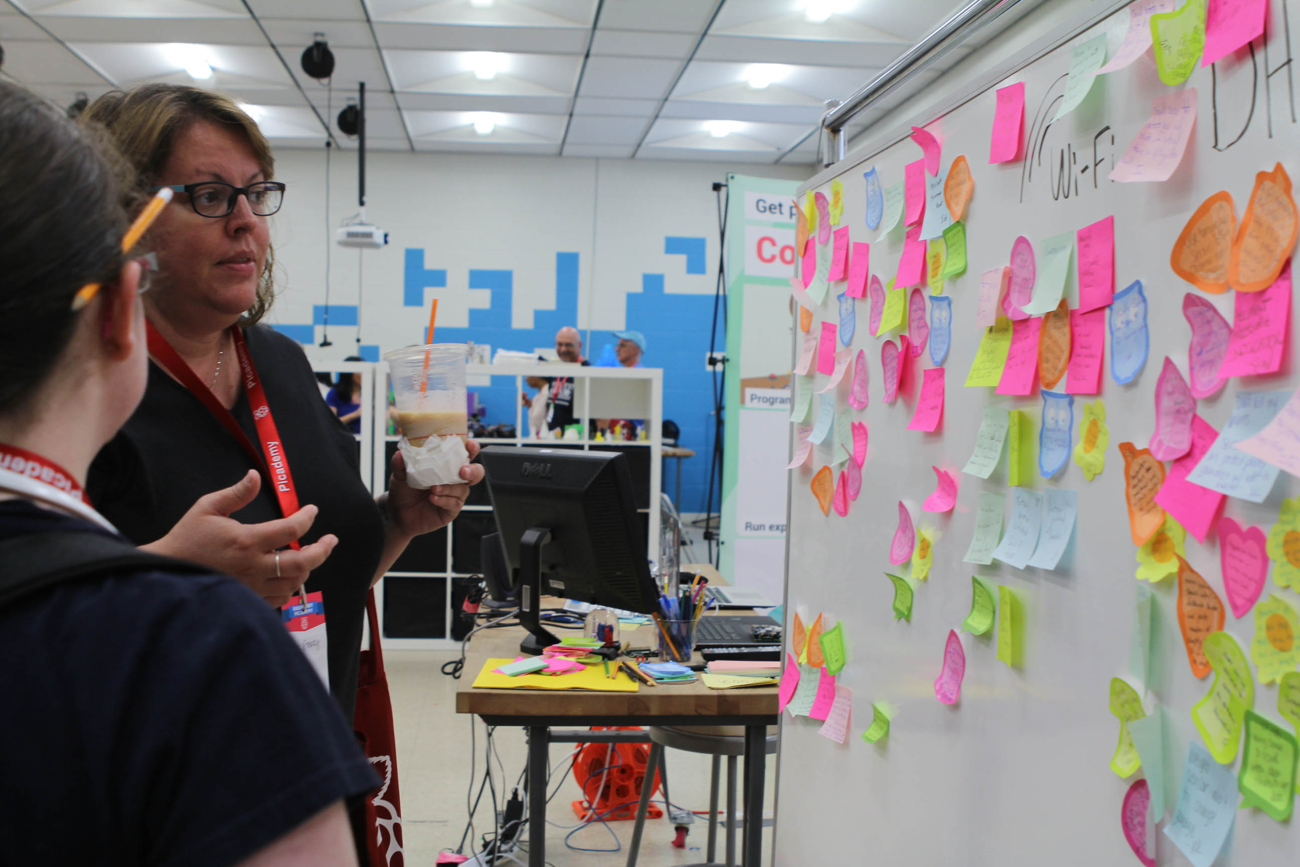 Image of a group designing a project, using post-it notes on a wall.